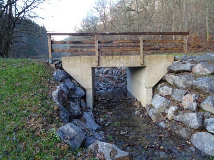 Brückenbauwerk ersetzt ehemalige Bachverrohrung und ermöglicht Bachlebewesen barrierefreies Wandern